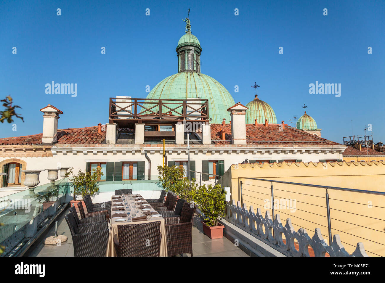 Church domes of the Church of San Simeone Piccolo and rooftop tables at the Hotel Carlton along the Grand Canal - Stock Image