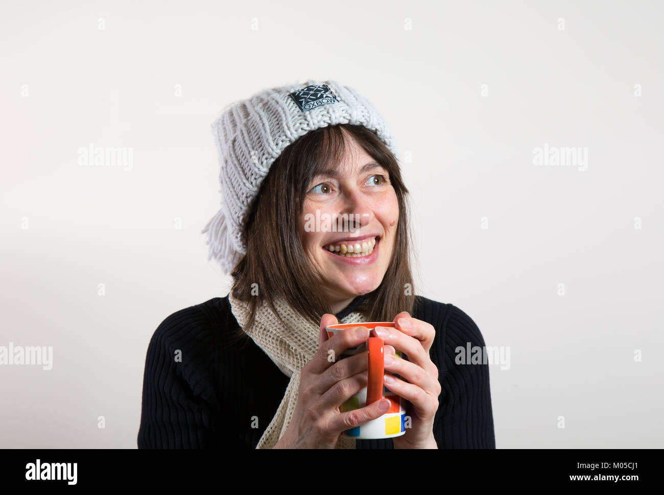 Inside portrait: happy female, front view, in beanie bobble hat, holding mug, warming hands. She looks up with big - Stock Image