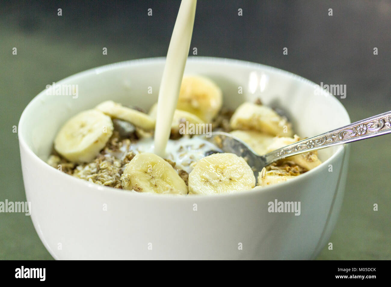 Breakfast idea bowl of cerial muesli with sliced banana and milk one of your five a day fruits and carbohydrates - Stock Image