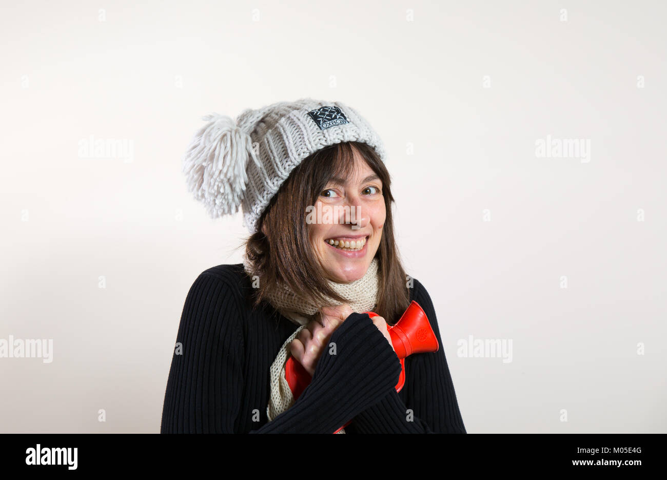 Interior front view happy caucasian female in 30s, in woolly hat, hugging hot water bottle close to chest. Nice - Stock Image