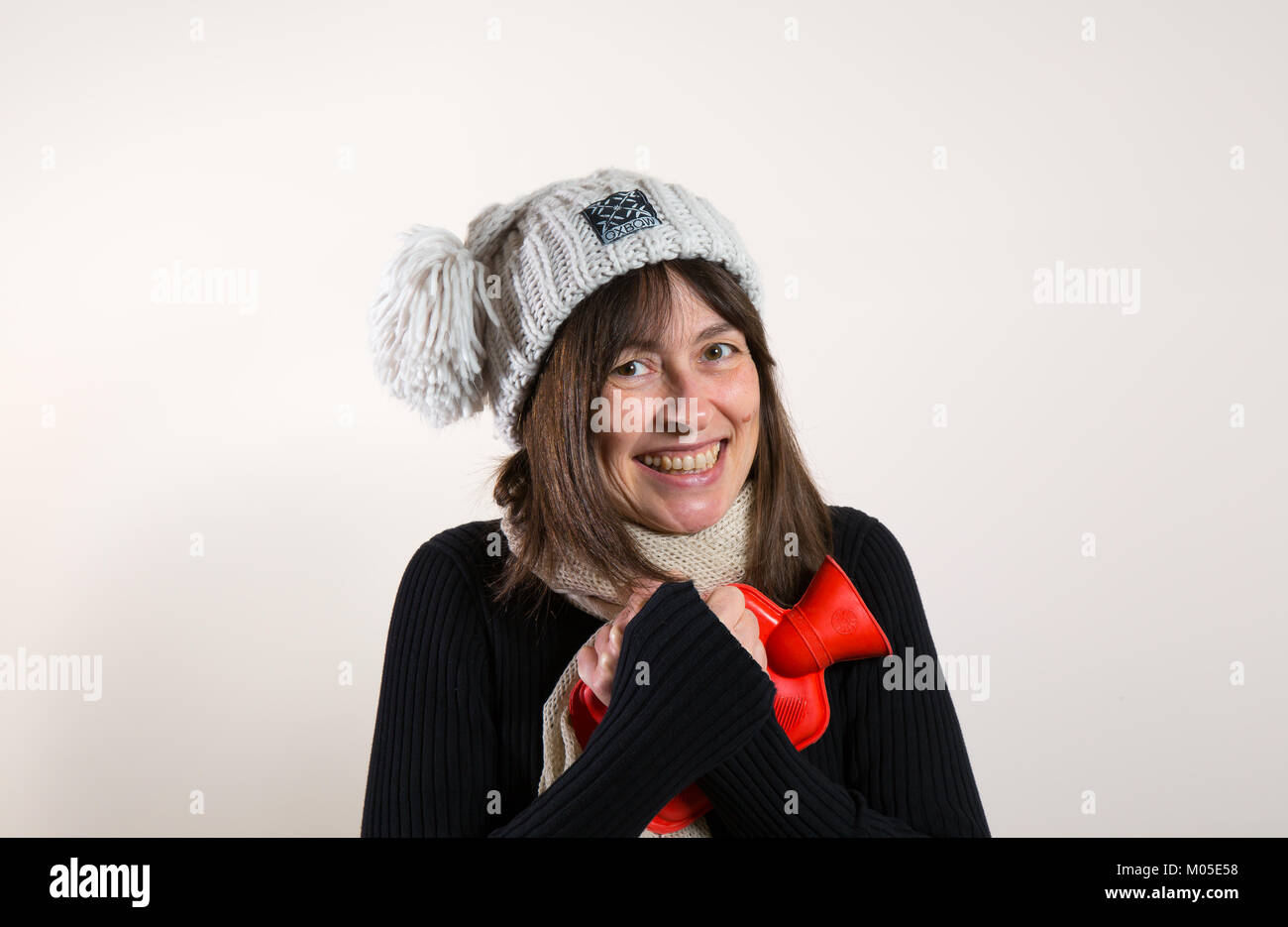 Interior front view of happy caucasian female in 30s, in woolly knitted bobble hat, hugging red hot water bottle - Stock Image