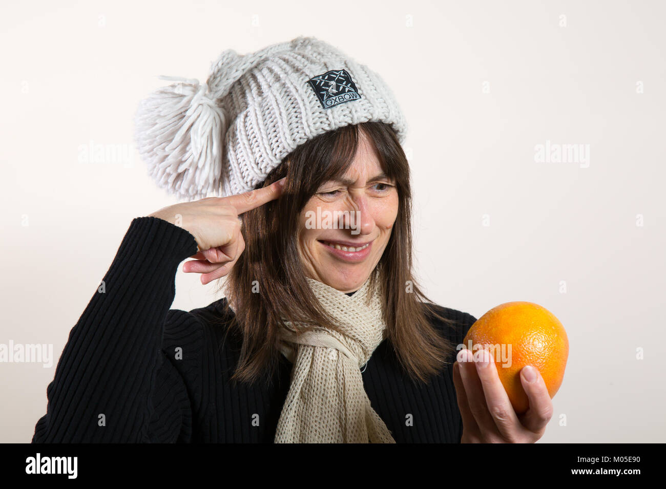 Puzzled female in woolly hat holding fruit, points to her head asking: What is it in her hand? A small grapefruit - Stock Image