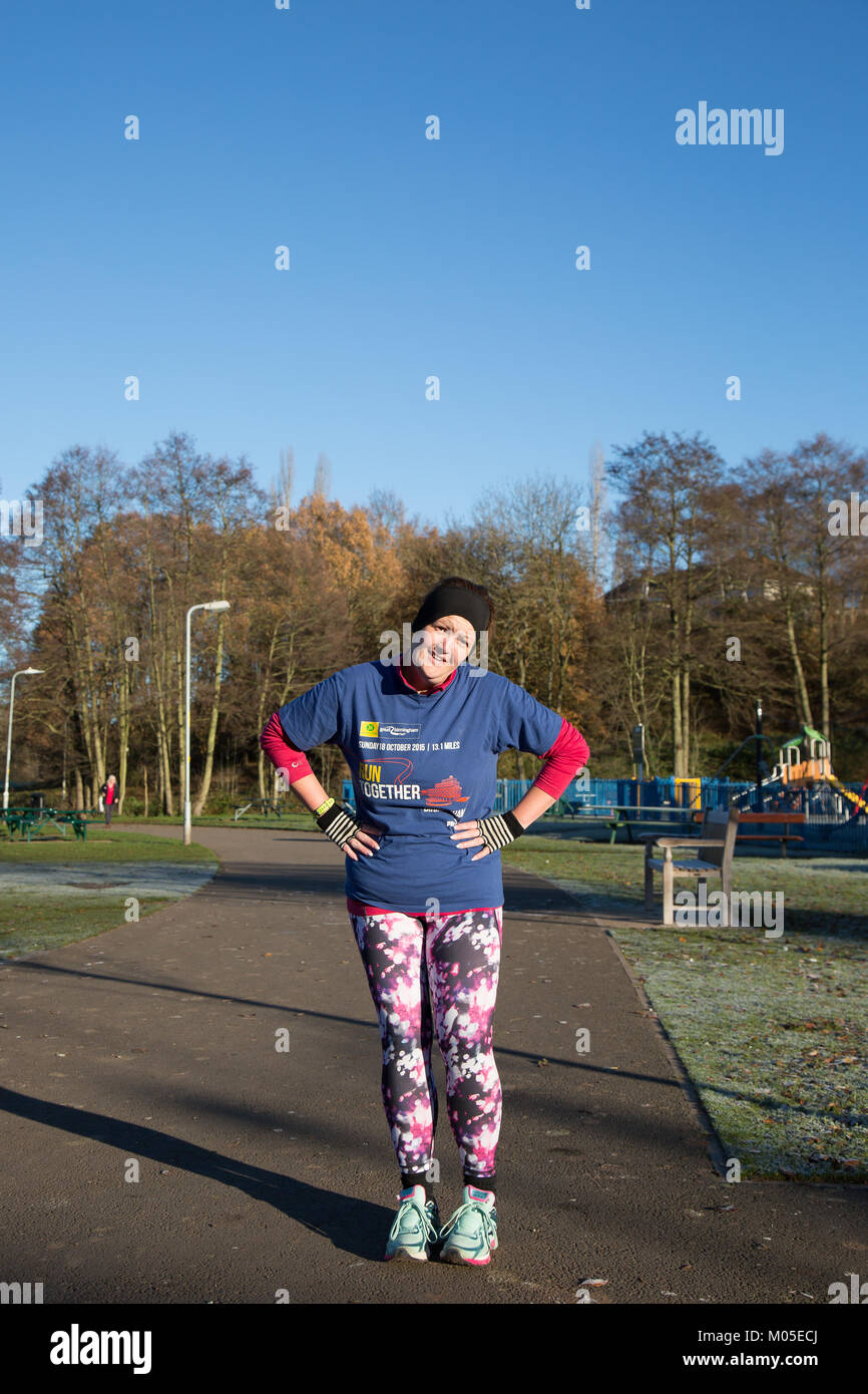 Obliging female runner, hands on hips, in jazzy, colourful leggings interrupts strict regime to pose for camera - Stock Image