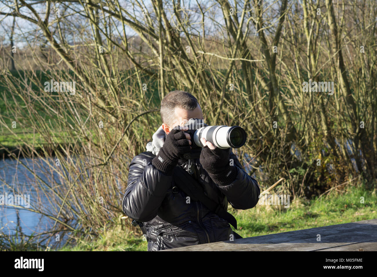 Professional male nature photographer taking photos on cold winter morning. Shooting outdoors, Canon equipment ready: - Stock Image