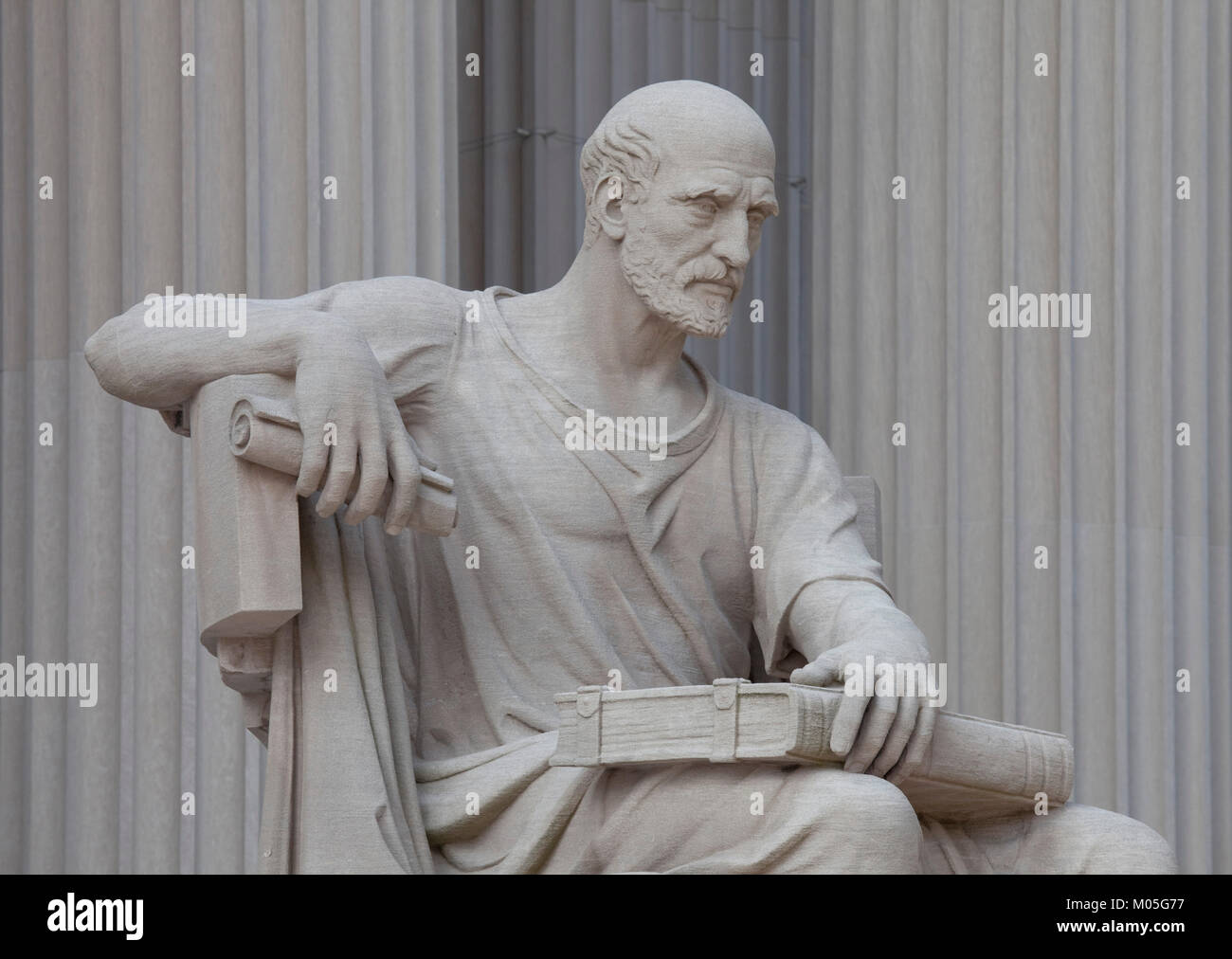Statue of old man with a scroll and closed book entitled 'Study the Past,' - Stock Image