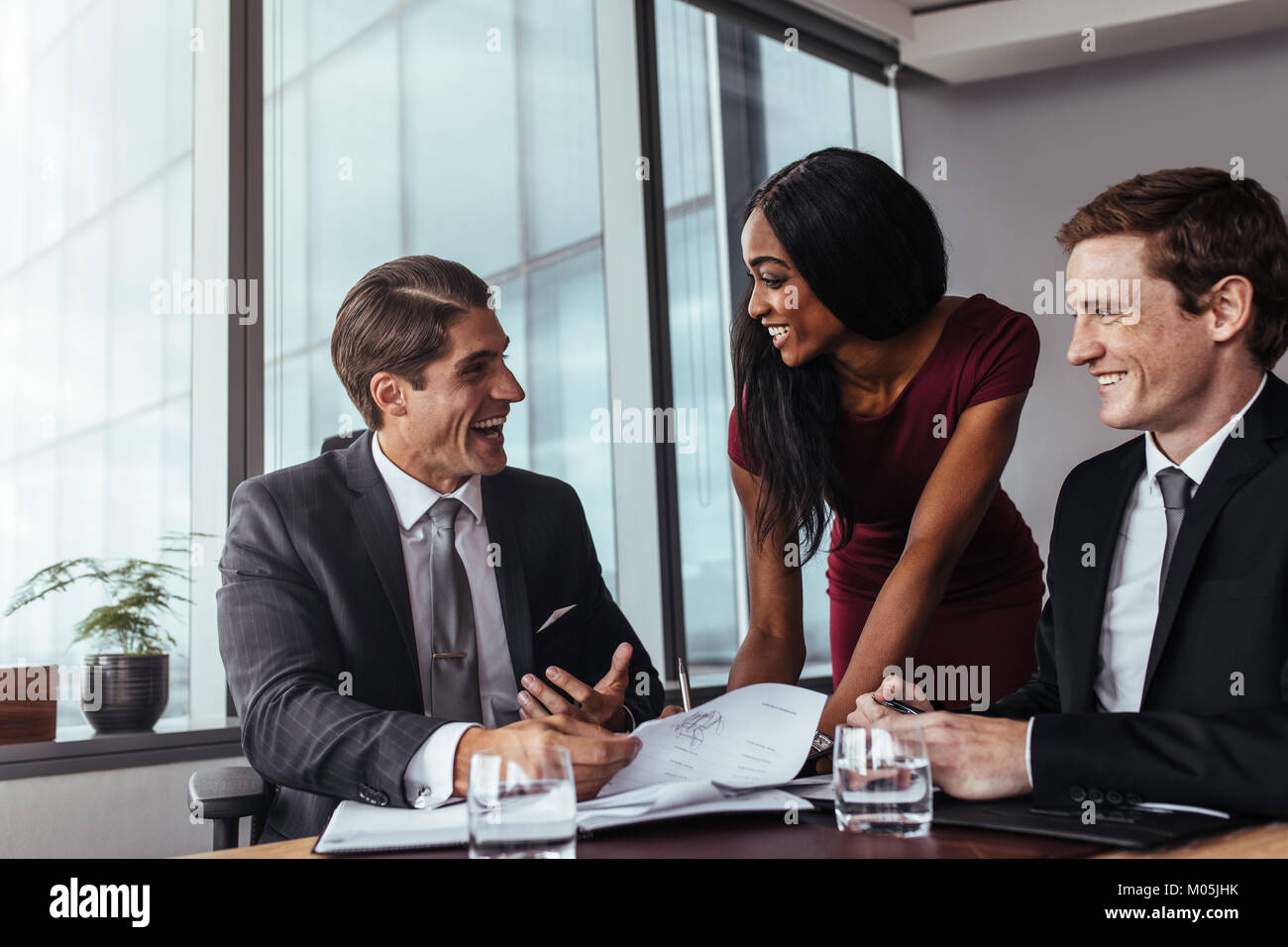 Corporate business professionals having a meeting in office and working on documents. Business people signing a - Stock Image