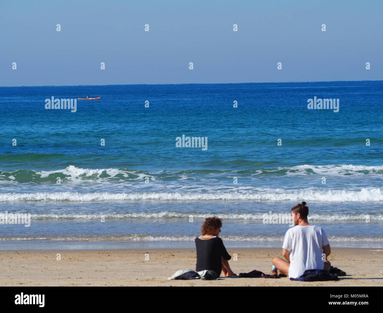 two Friends sitting on the beach sand on a perfect clear day and