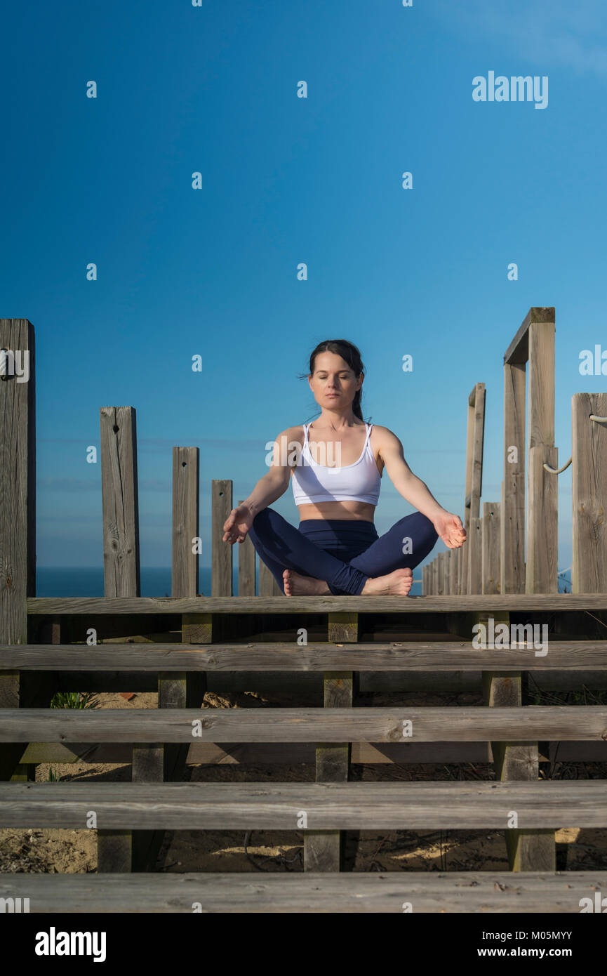 woman meditating in the lotus position sitting on wooden steps by the sea. - Stock Image