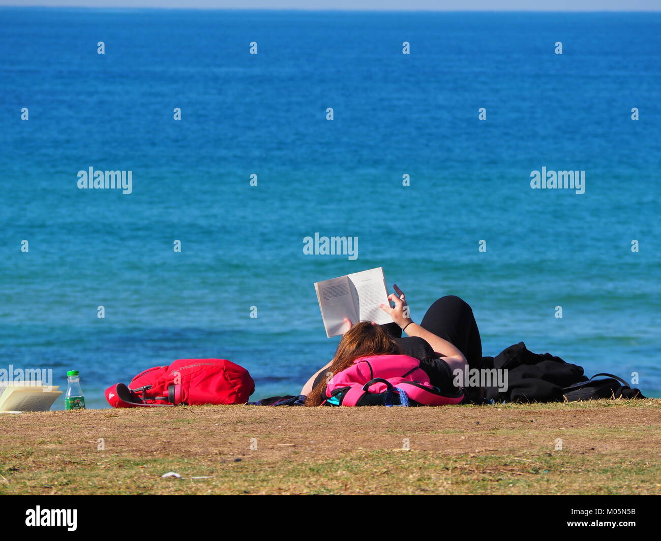 girl lying in the sun at the promenade near the beach in front of the sea on a perfect day with clear blue sky Stock Photo