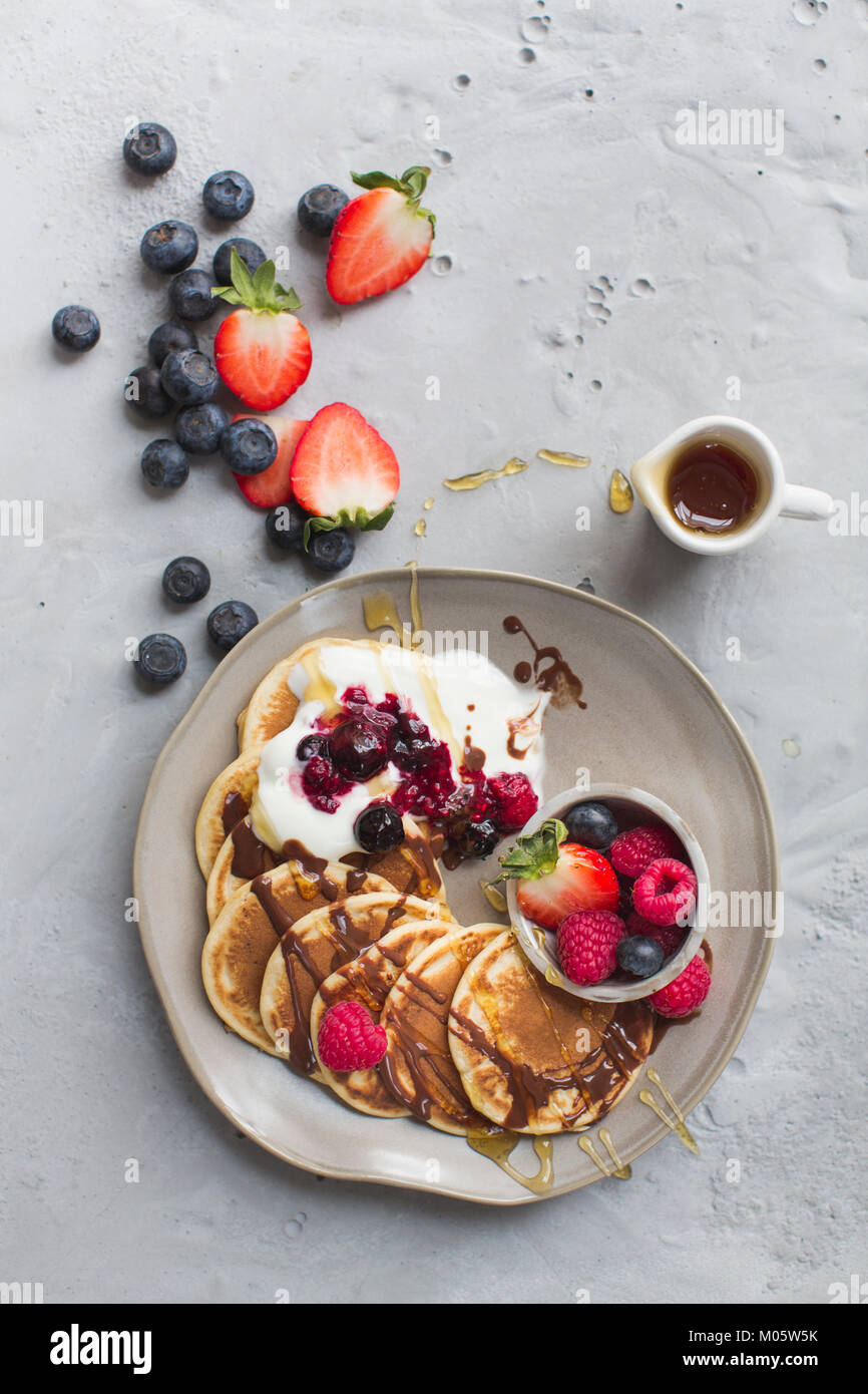 Pancakes with fresh fruits and chocolate sauce and maple syrup - Stock Image