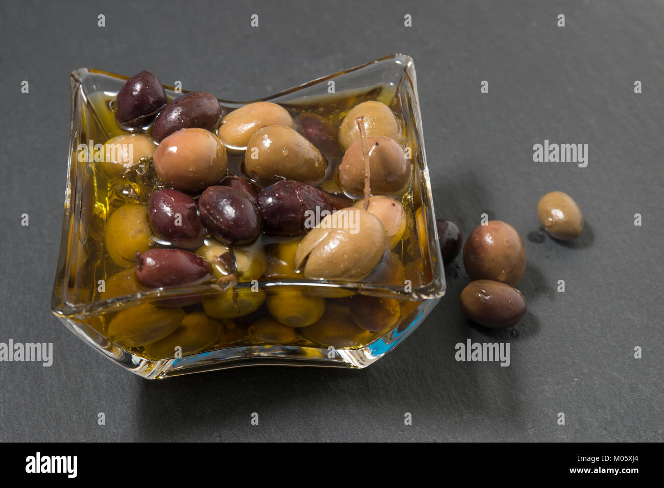 Olives with olive oil on a shale stone. - Stock Image