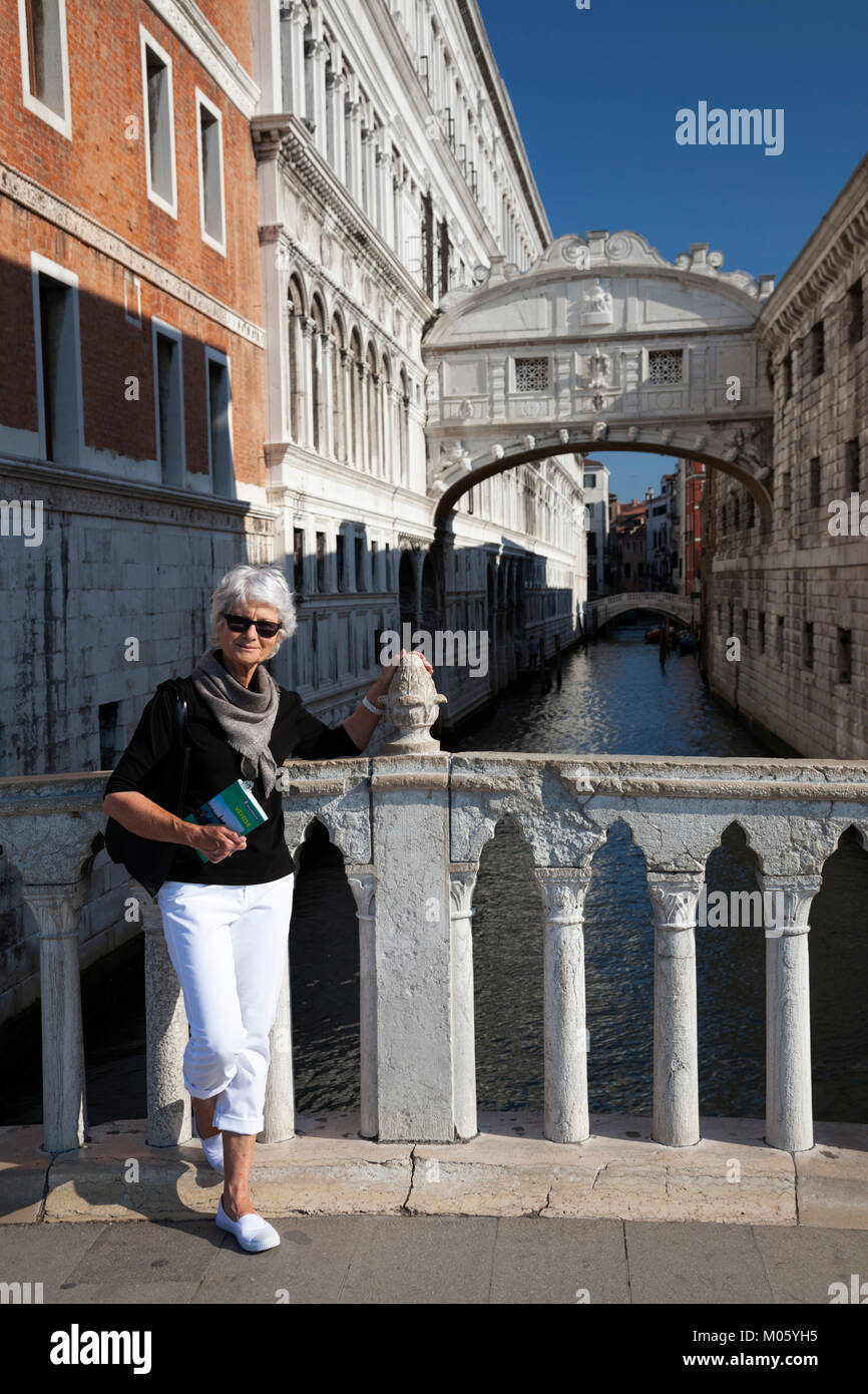 Equipped with her Michelin guide book, a senior tourist posing in front of the bridge of sighs at Venice (Italy). - Stock Image