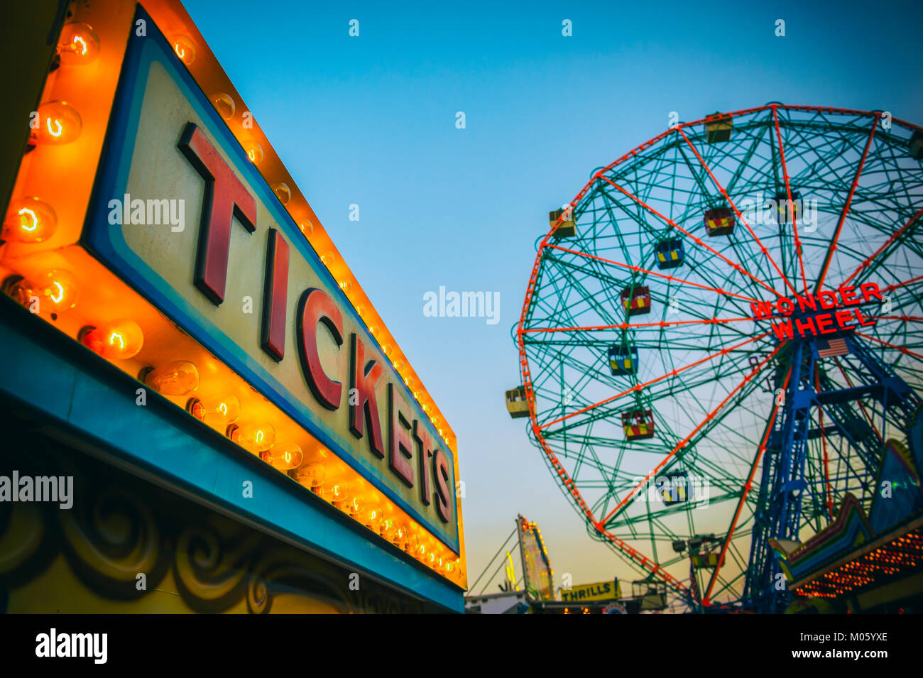 NEW YORK CITY - AUGUST 20, 2017: The bright lights of the amusement park at Coney Island in Brooklyn glow in front - Stock Image
