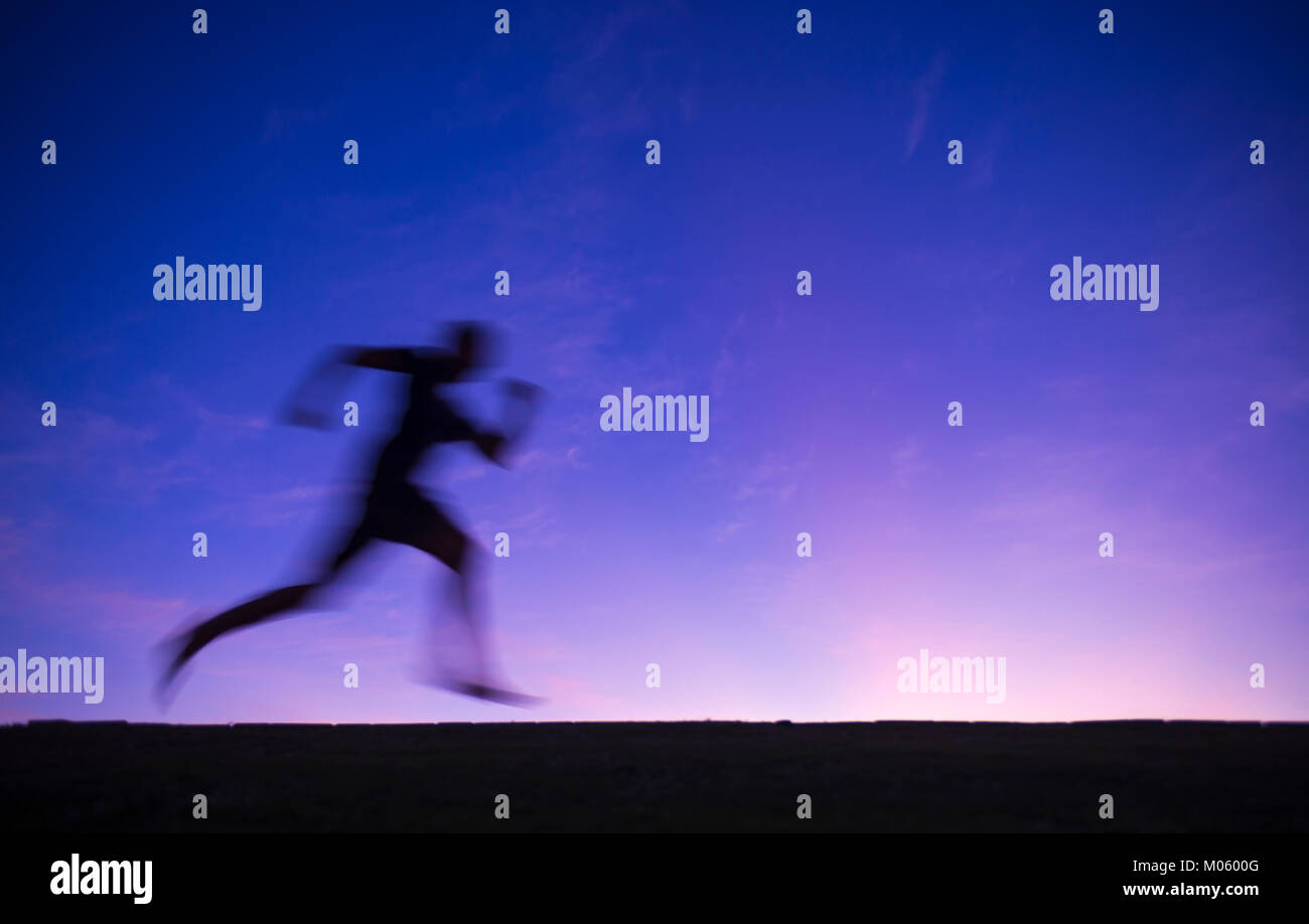 Silhouette blur of a runner passing across a purple twilight sunset sky background - Stock Image