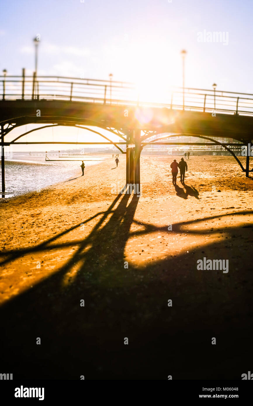 Mature couple walk together under Cleethorpes Pier on a bright winters morning. Cleethorpes, England, UK - Stock Image
