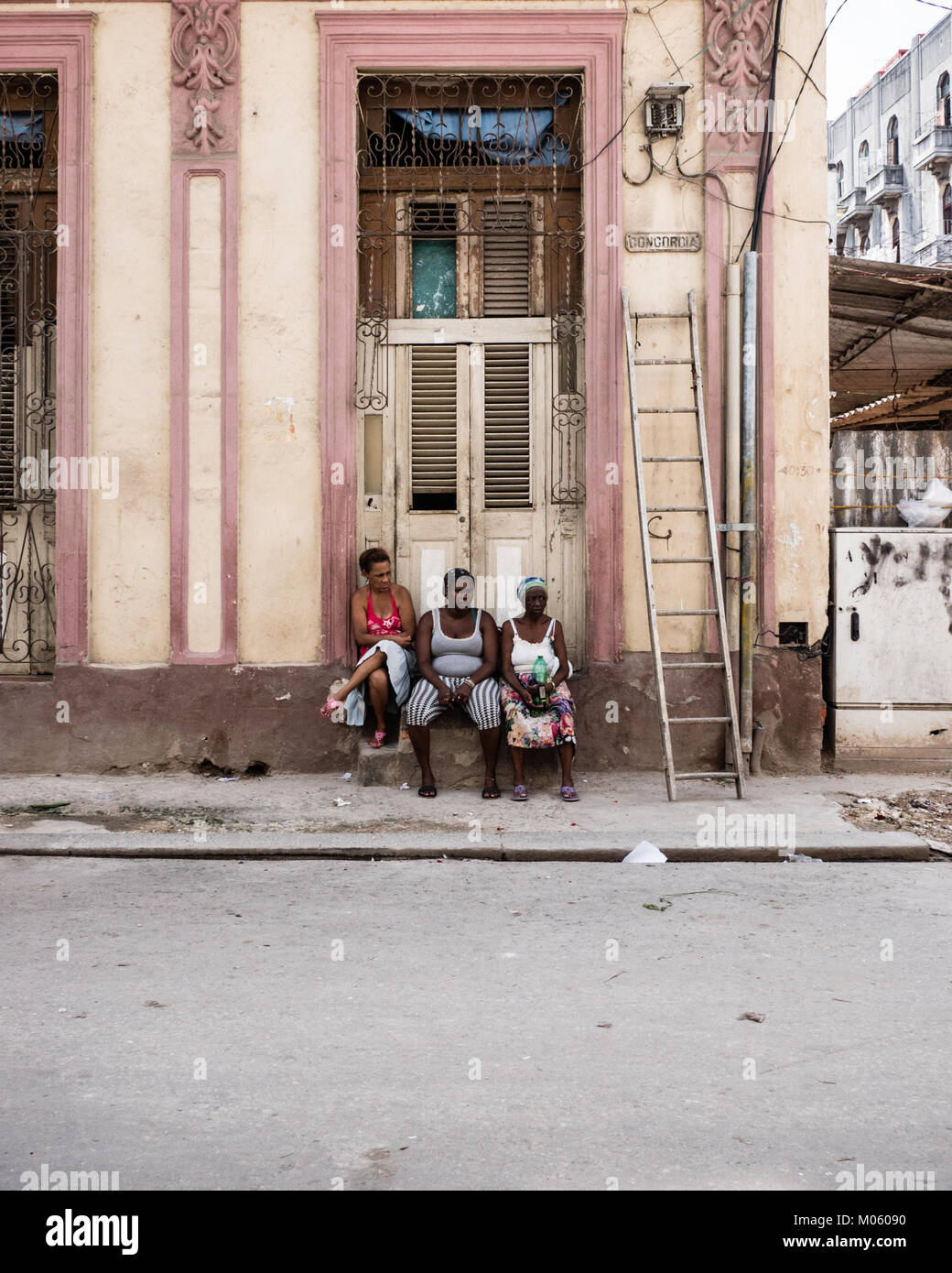 Three Afro Caribbean females relax on a stone step outside a doorway to a property in Havana, Cuba - Stock Image