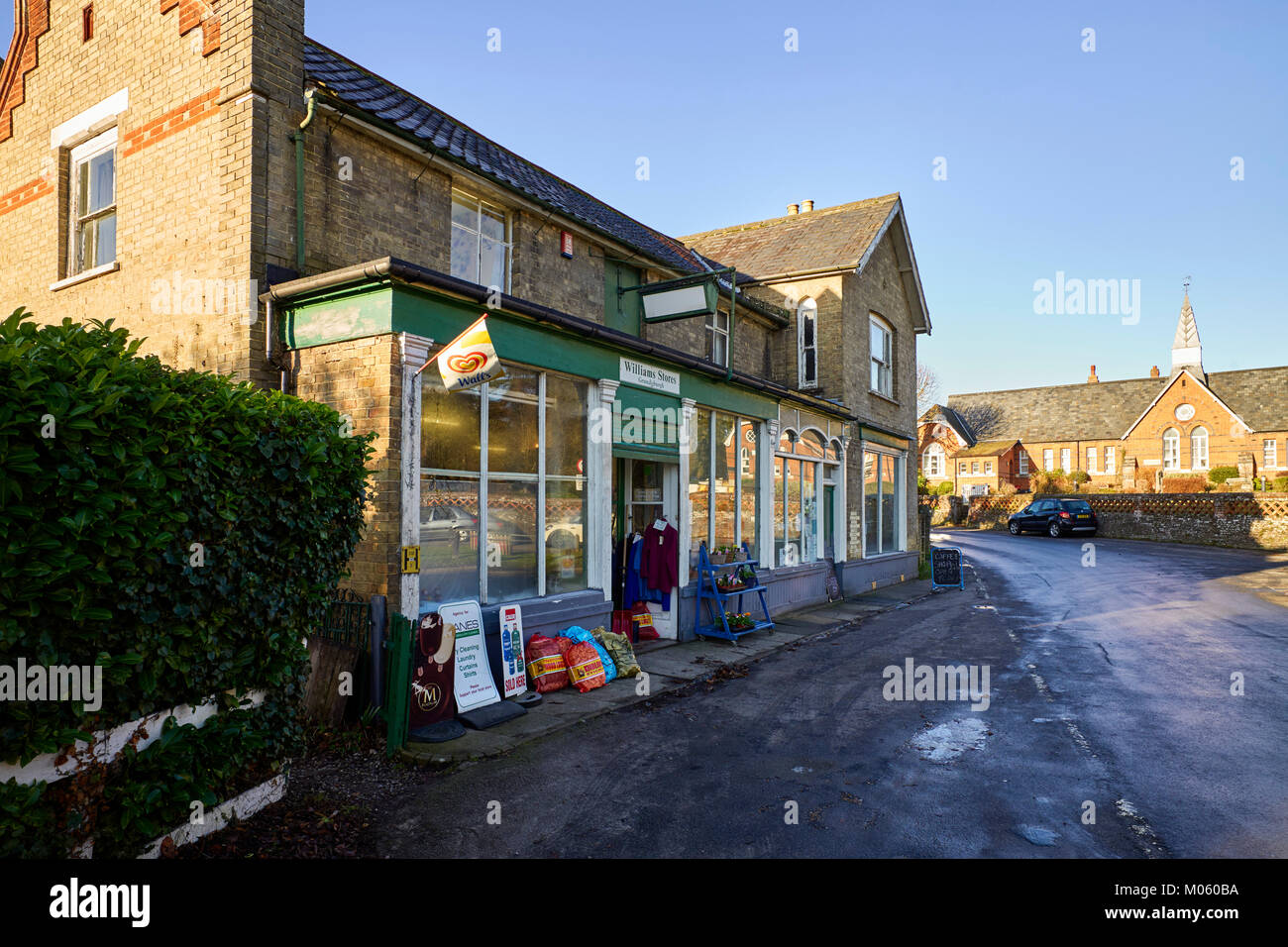 The village shop with old school in the background in the Suffolk village of Grundisburgh - Stock Image