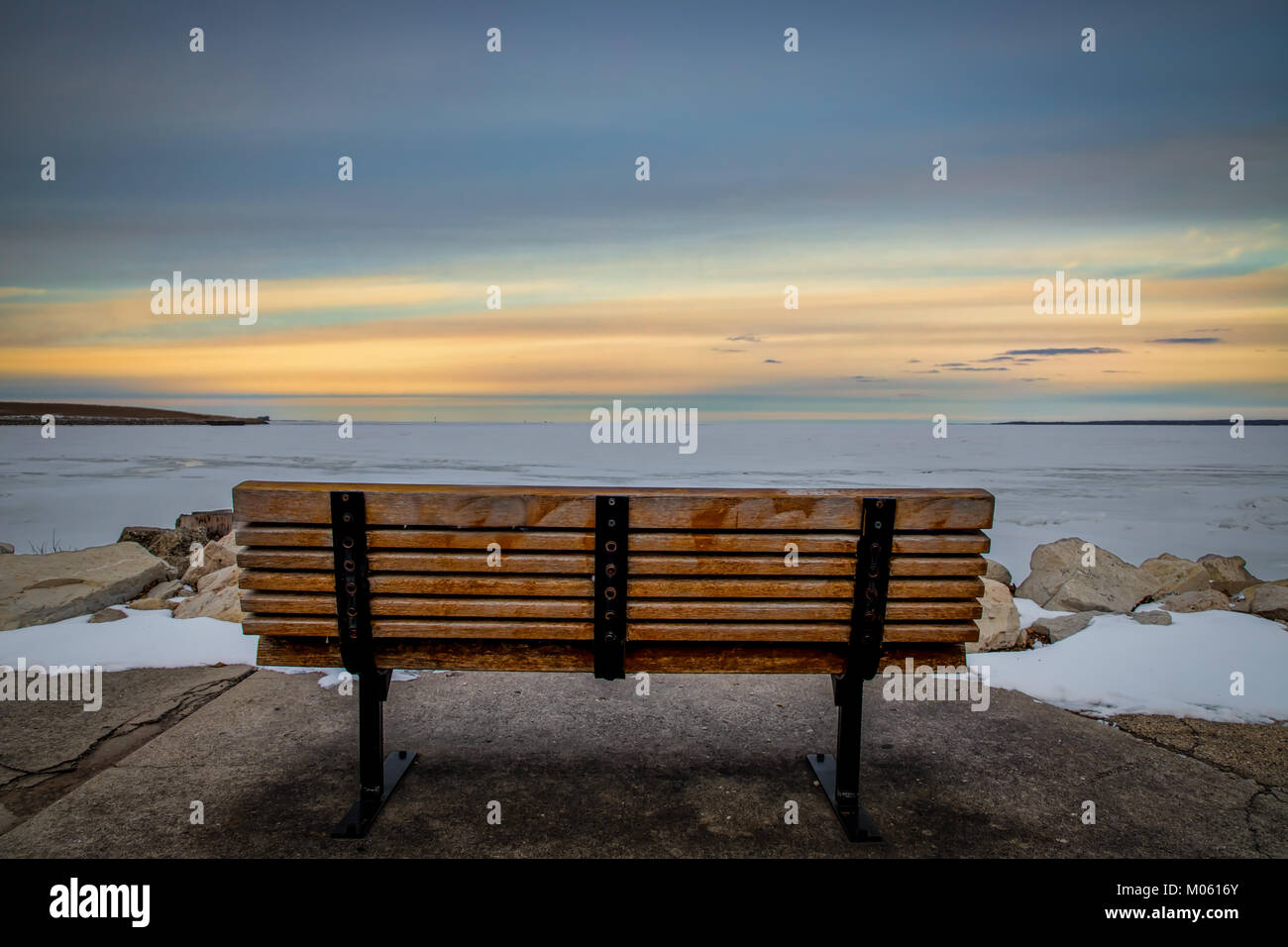 A park bench overlooking the frozen waters of Green Bay, WI. - Stock Image