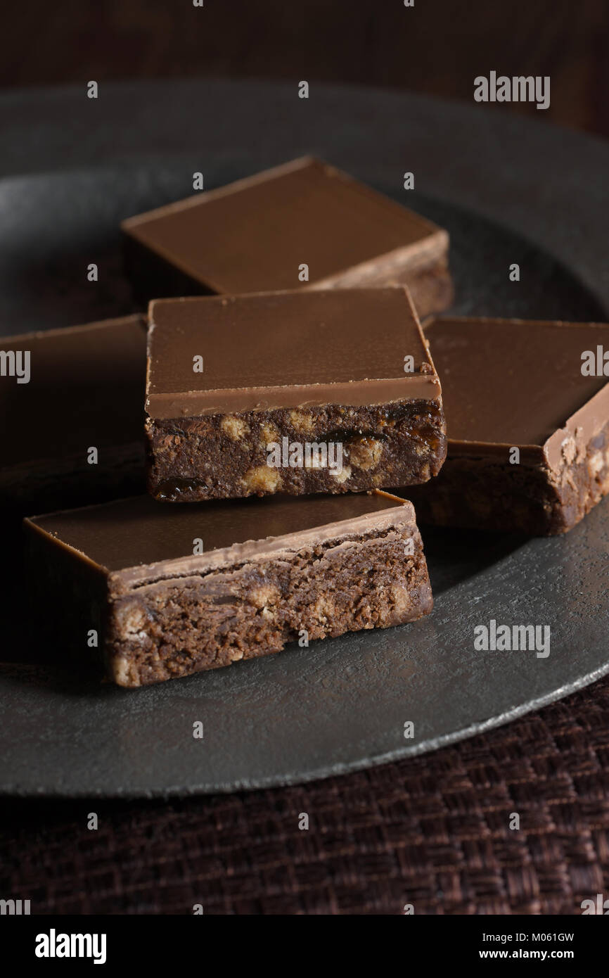 Tiffin or fridge cake a confection made with cocoa crushed biscuit dried fruit and melted chocolate then chilled - Stock Image