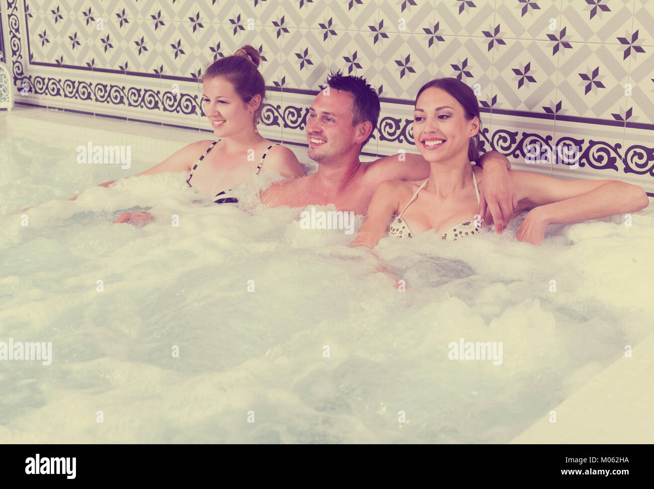 Company of three people relaxing enjoying jacuzzi hot tub bubble ...