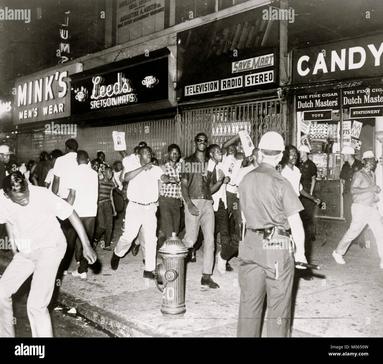 The fatal shooting of Powell stirred Negro rioters to race through Harlem streets carrying pictures of Lt. Gilligan - Stock Image