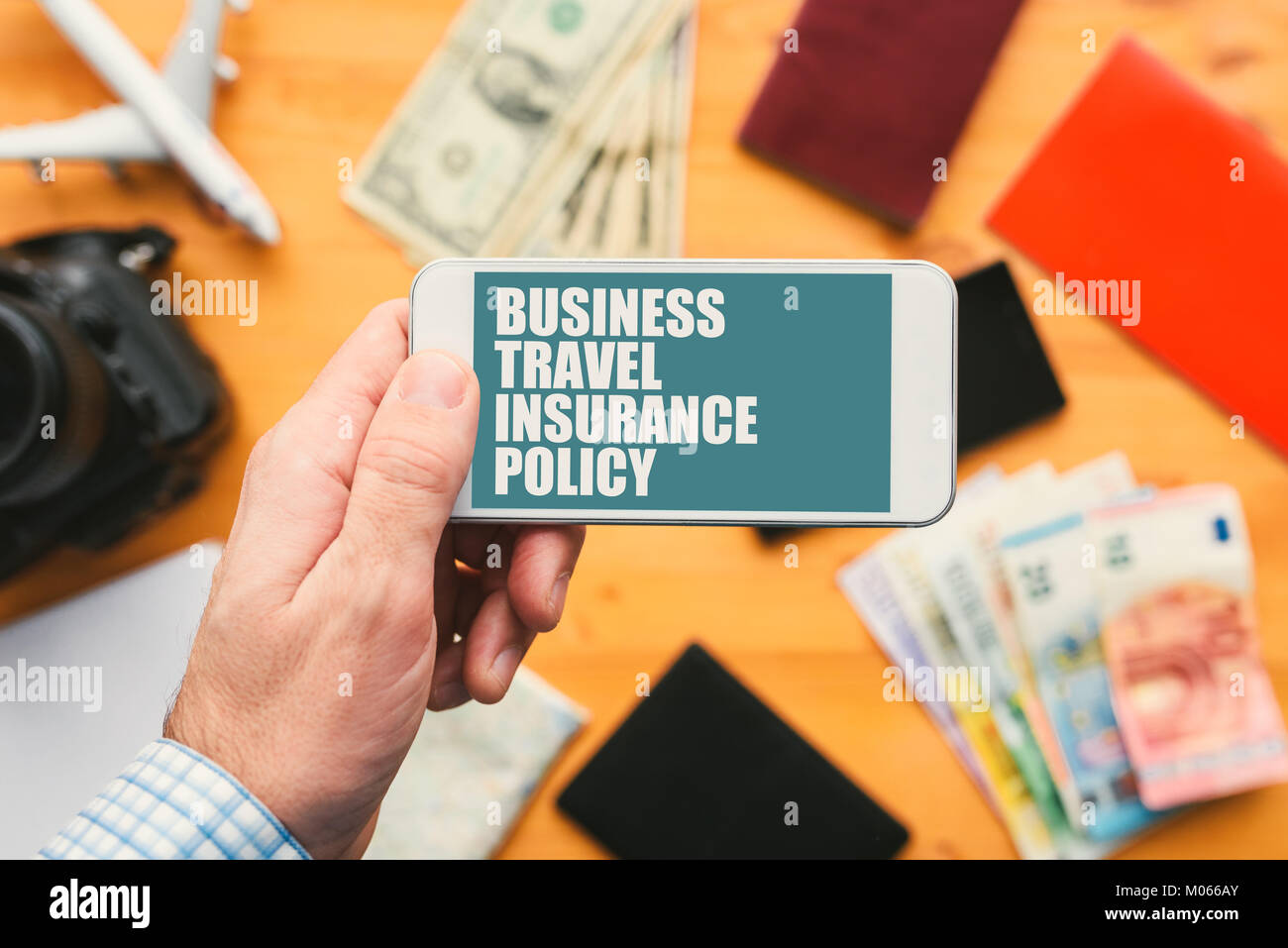 Business travel insurance policy online mobile app. Man holding smartphone with mock up application screen related - Stock Image