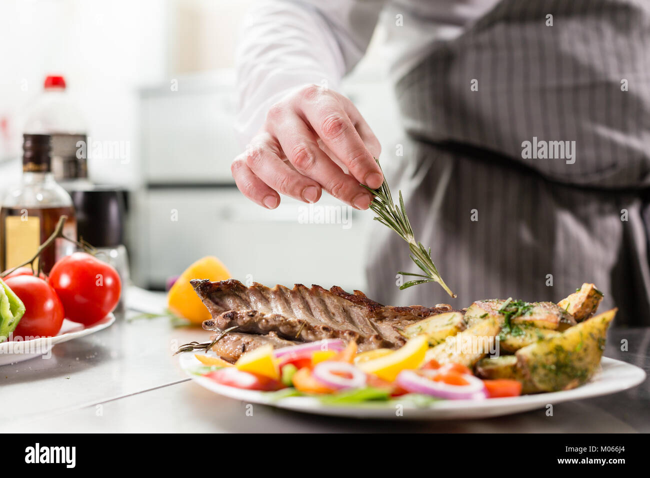 decorated with a sprig of rosemary. the chef prepares in the restaurant. Grilled rack of lamb with fried potatoes - Stock Image