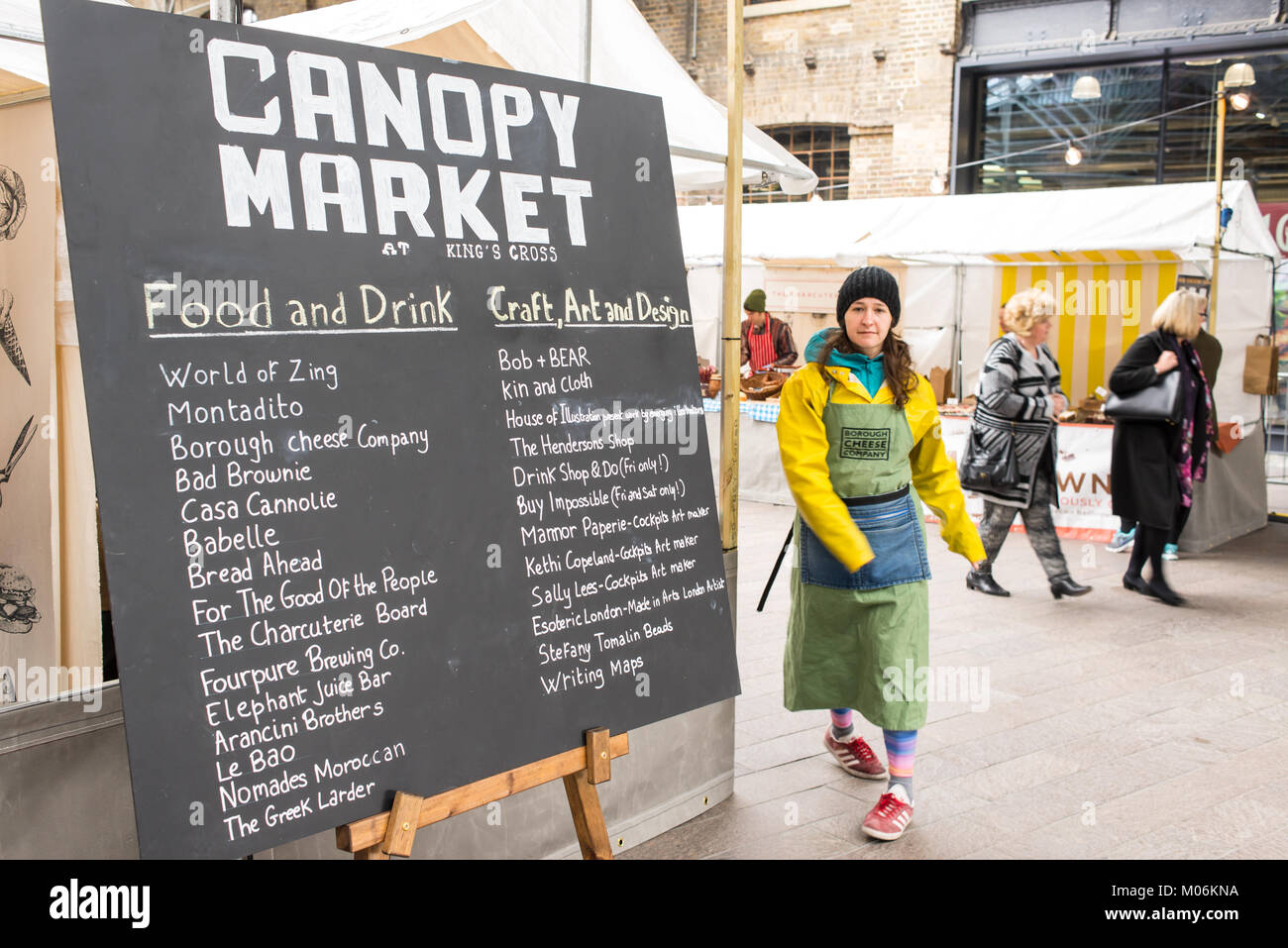 Stall owner walking in front of a billboard promoting the Canopy Market, King's Cross, London. Canopy market - Stock Image