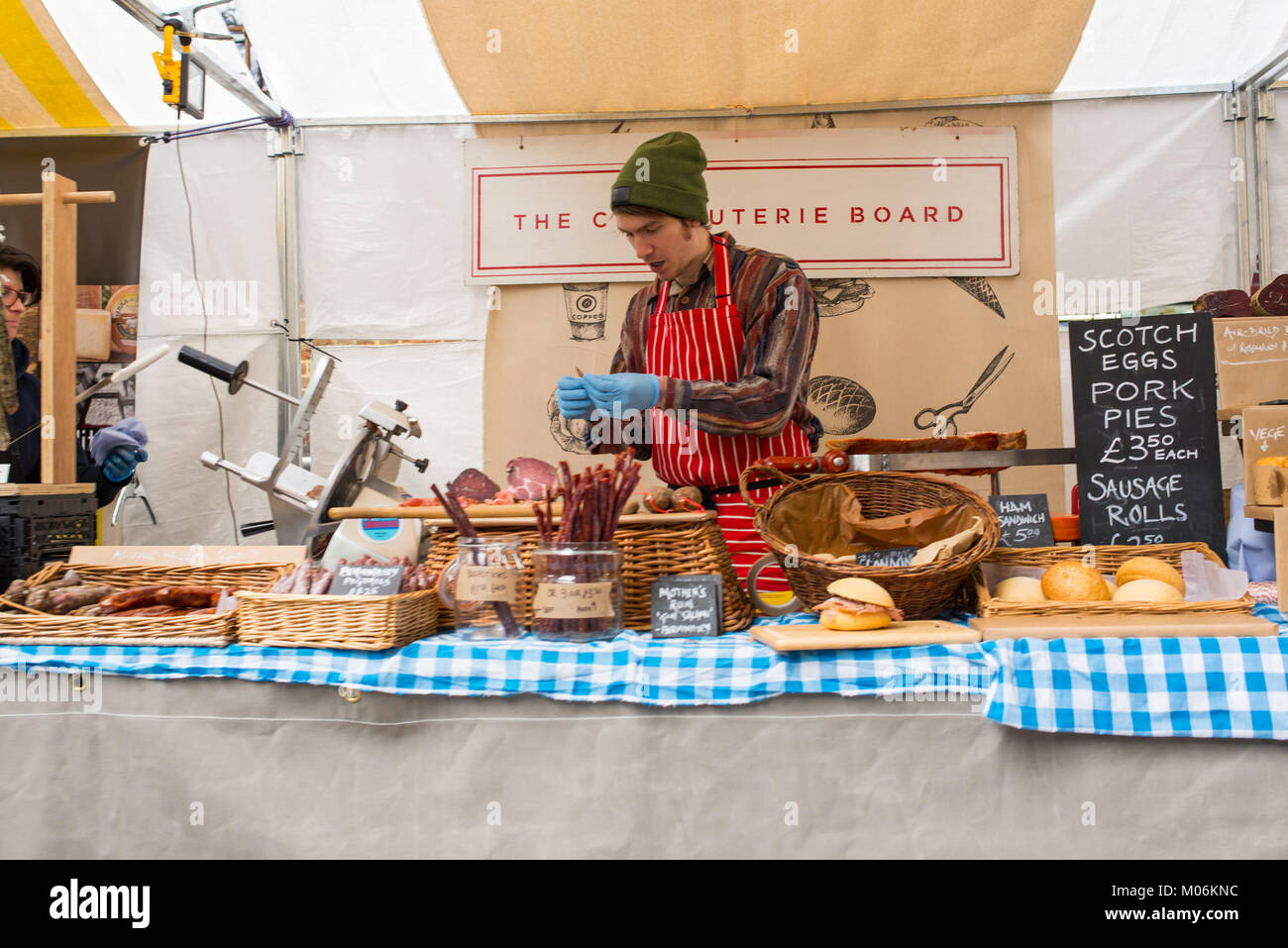 Hipster charcuterie stall serving cured meat and sausage rolls at the Canopy Market, King's Cross, London. Canopy - Stock Image