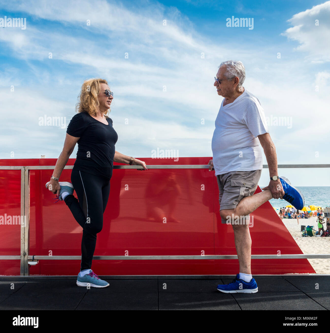 Model Released - Mature heterosexual couple stretching quadriceps on beach-side gym - Stock Image