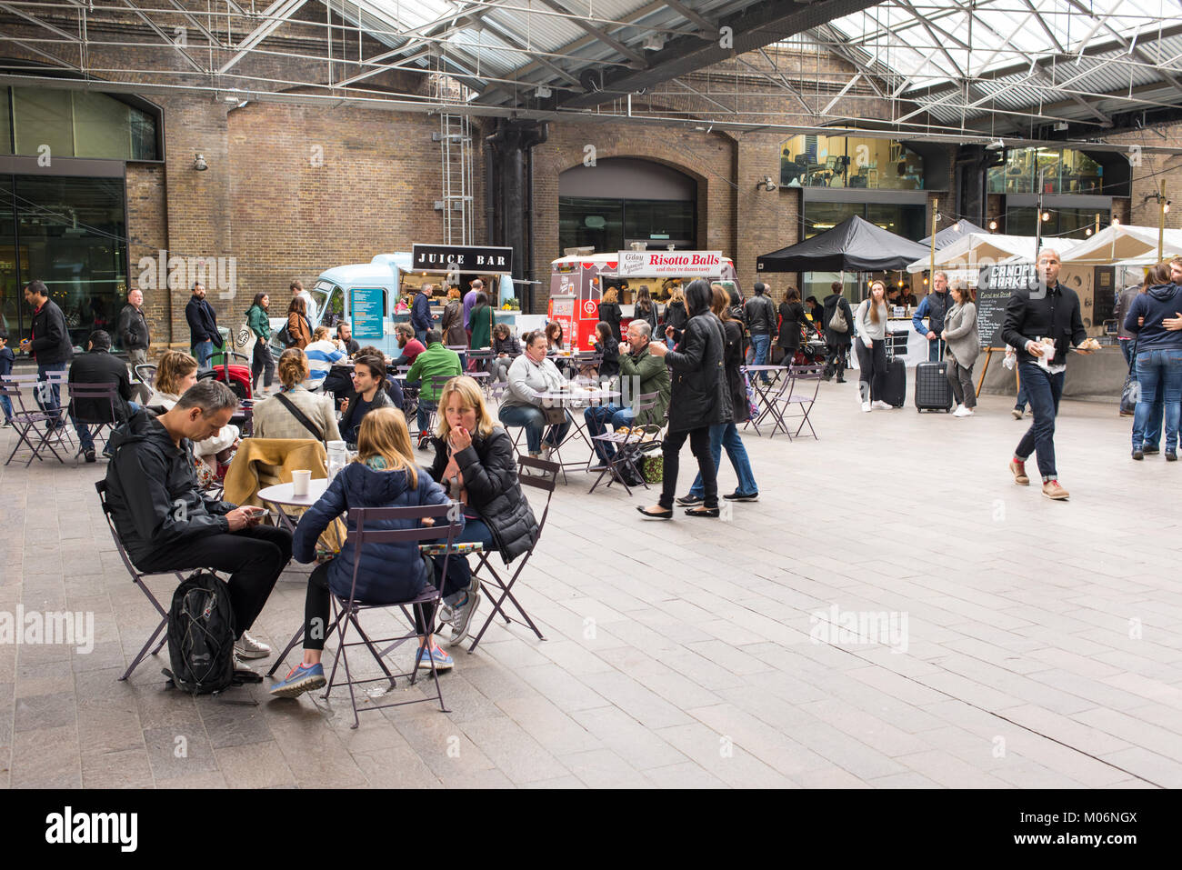 People eating and sitting in the inddor area of the Canopy Market, King's Cross, London. Canopy market is a - Stock Image