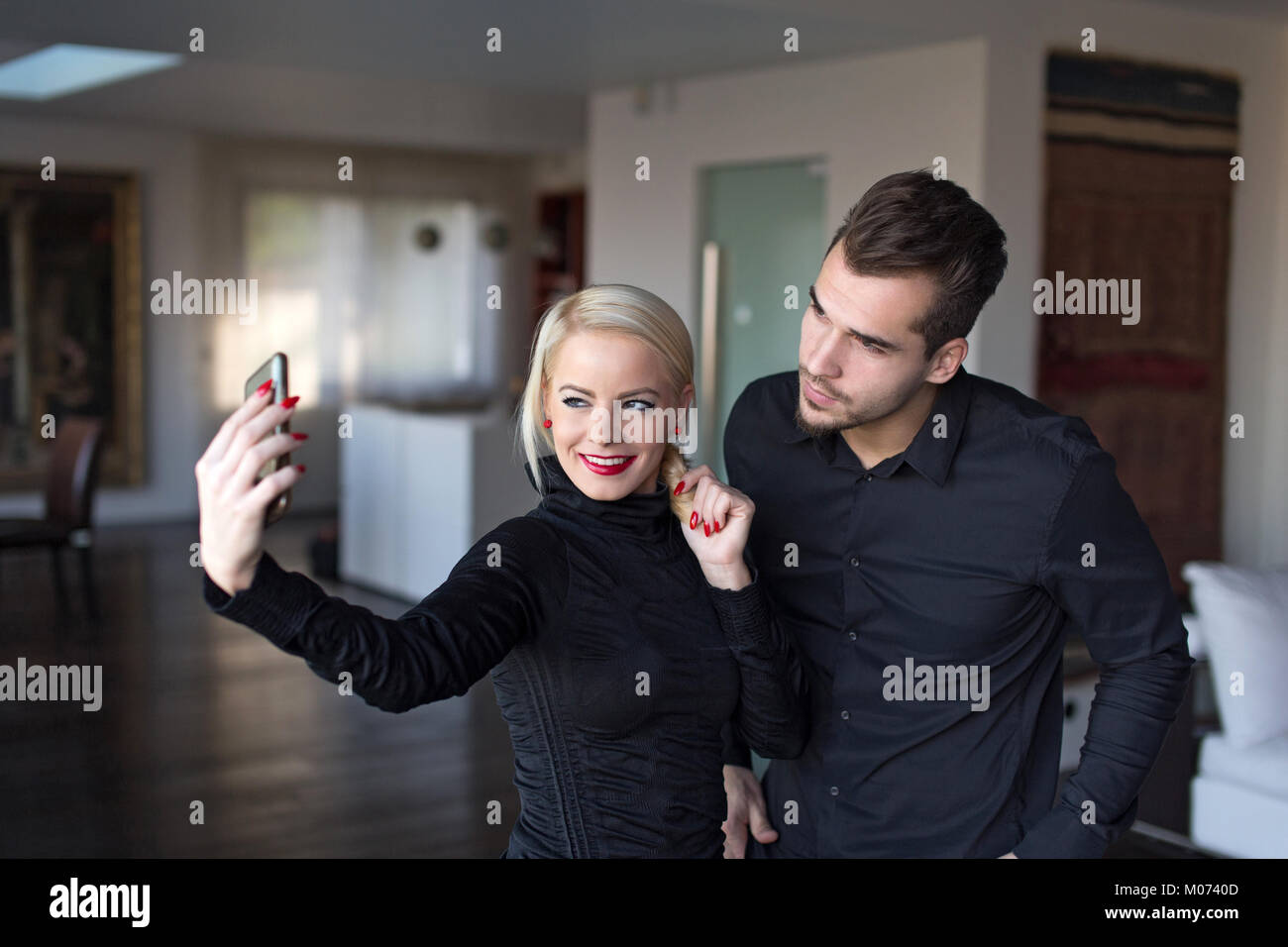 Happy young stylish couple in black outfit taking selfie indoor - Stock Image