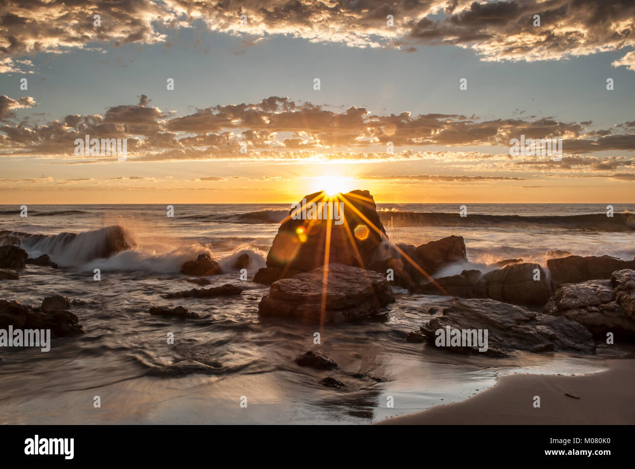 A sun burst sunset at O'Sullivan Beach, South Australia, complete with water spraying, crashing waves - Stock Image