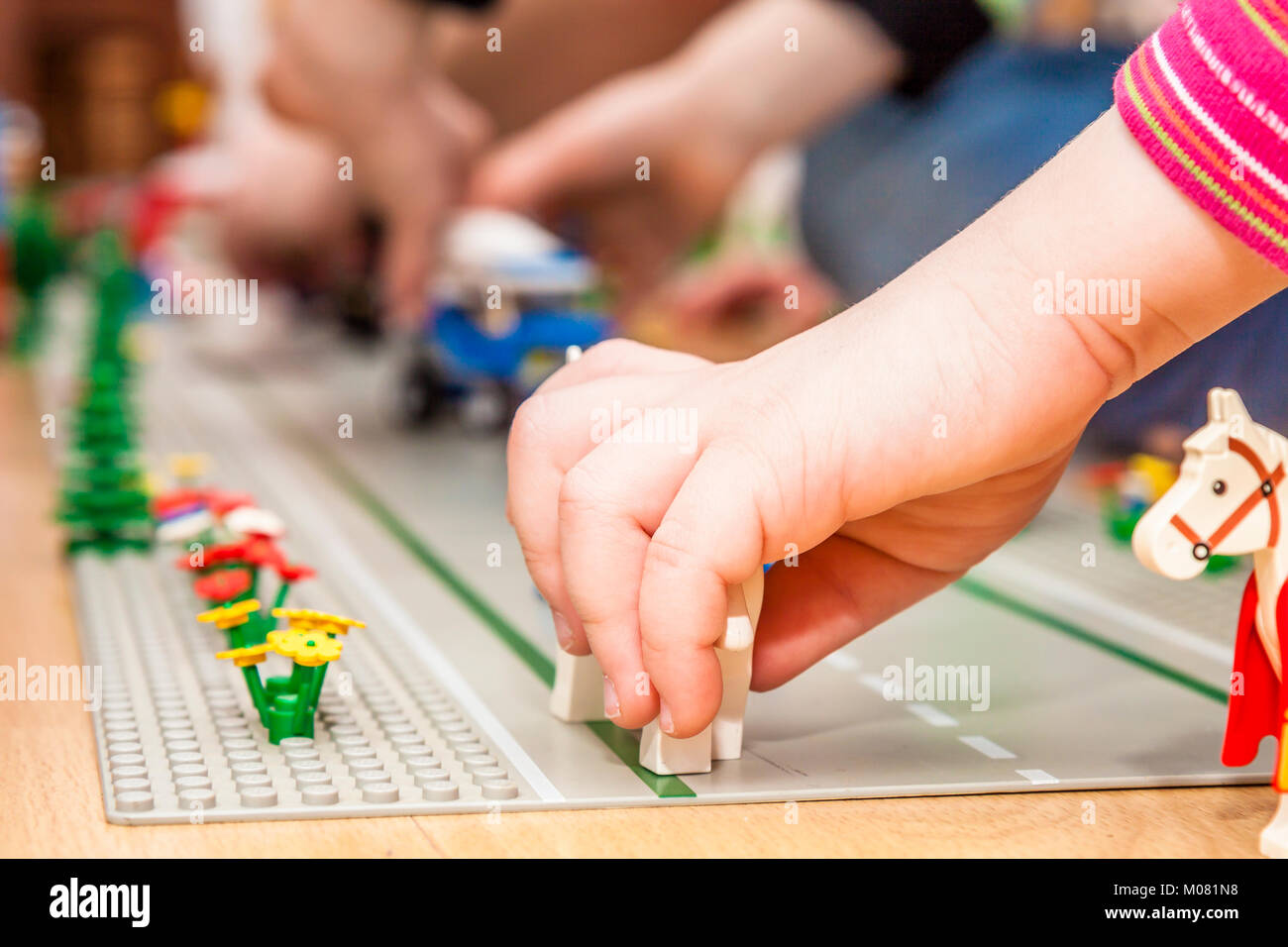 Preschooler girl playing with colorful toy blocks and bricks - Stock Image