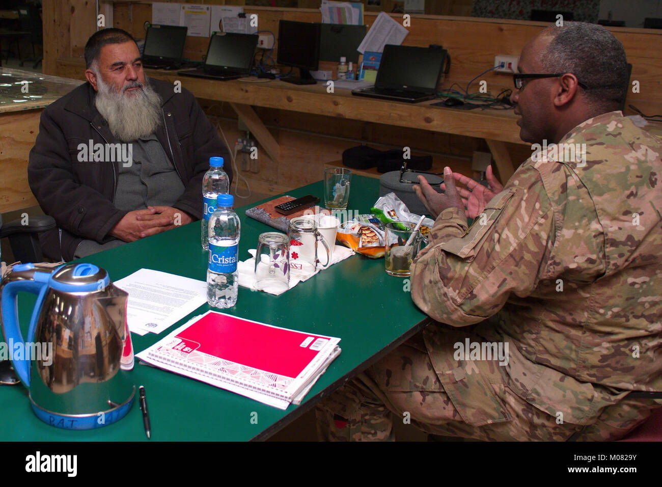 Afghan National Police (ANP) 303rd Zone G1 Commander Col. Zikarullah meets with Task Force Southeast Police Advisor - Stock Image