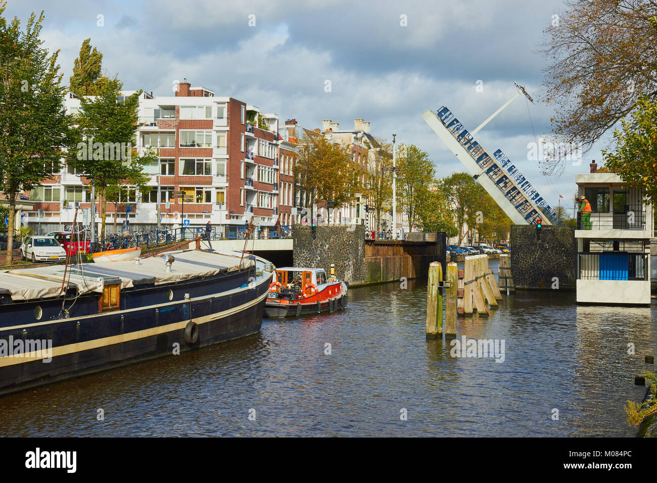 Tug boat guiding a barge through Hortusbrug a bascule bridge across Nieuwe Herengracht canal, Amsterdam, Netherlands - Stock Image