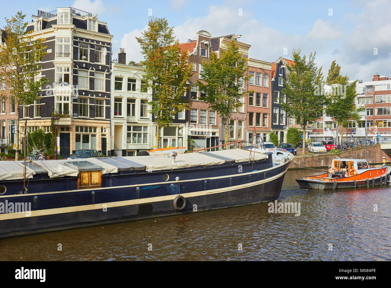 Tug boat guiding a barge along Nieuwe Herengracht canal, Amsterdam, Netherlands - Stock Image