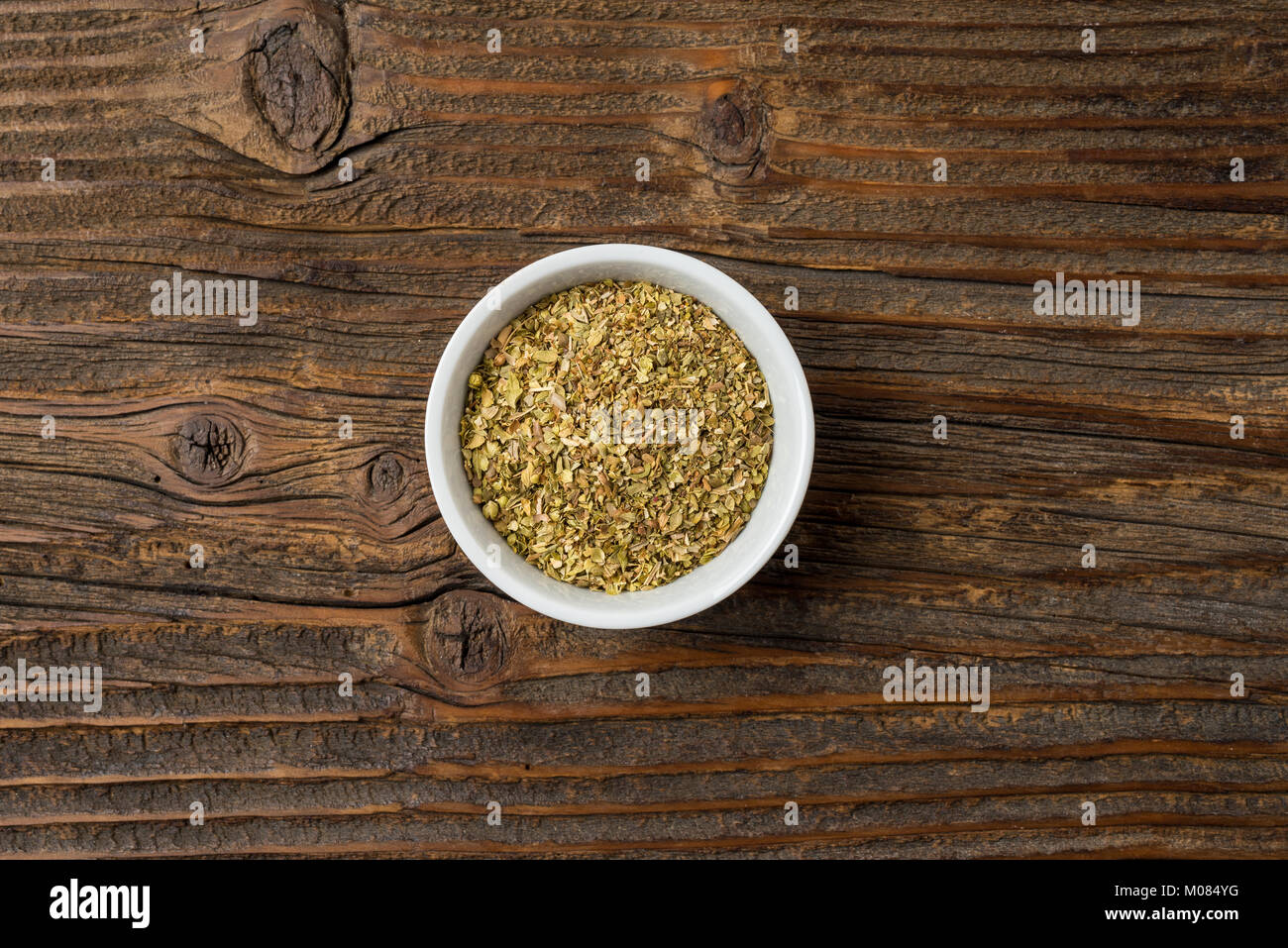 Dried marjoram in white bowl on an old wooden table - Stock Image