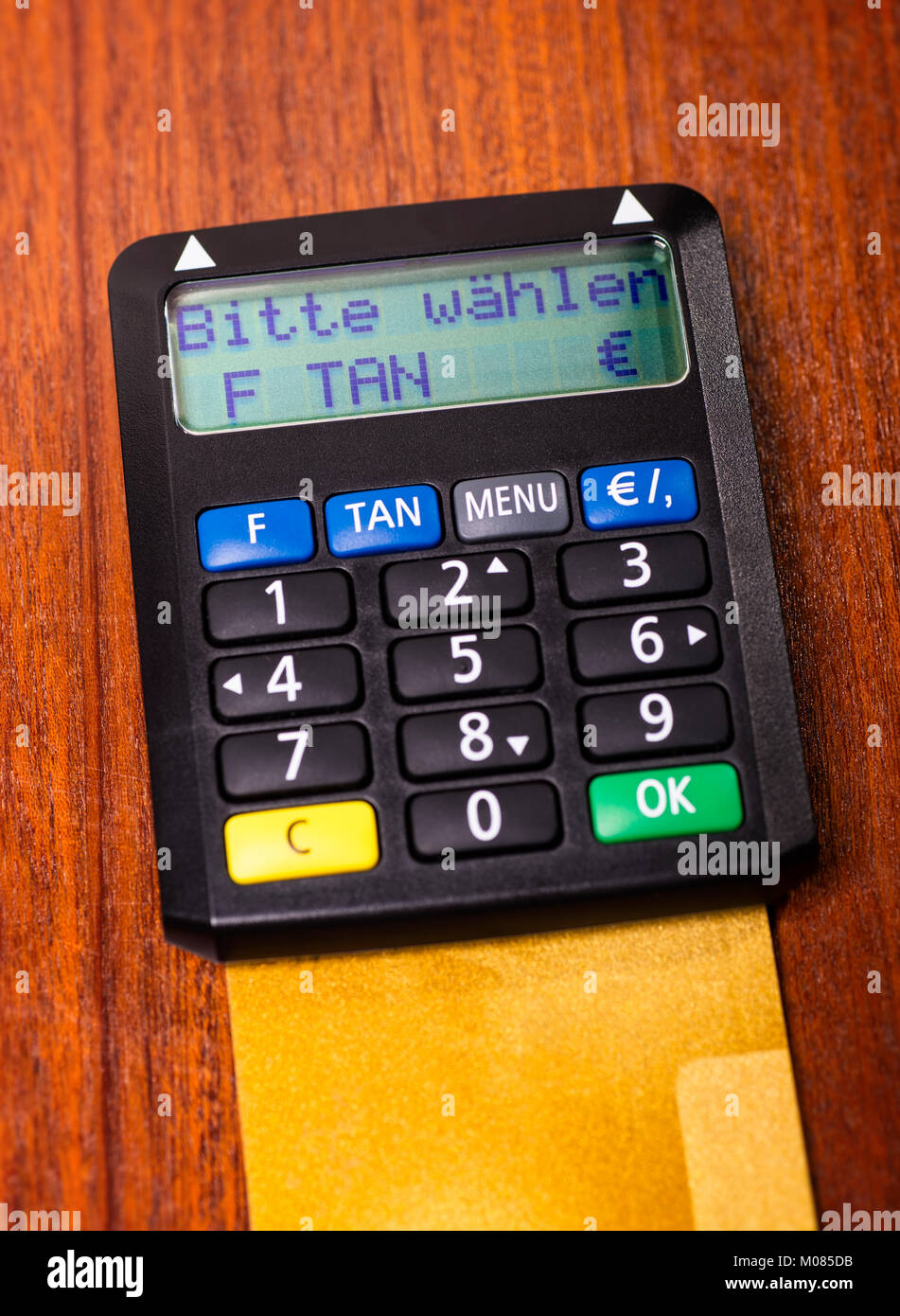 Tan generator with credit card lying on a desk and the request 'please select' on the display - Stock Image
