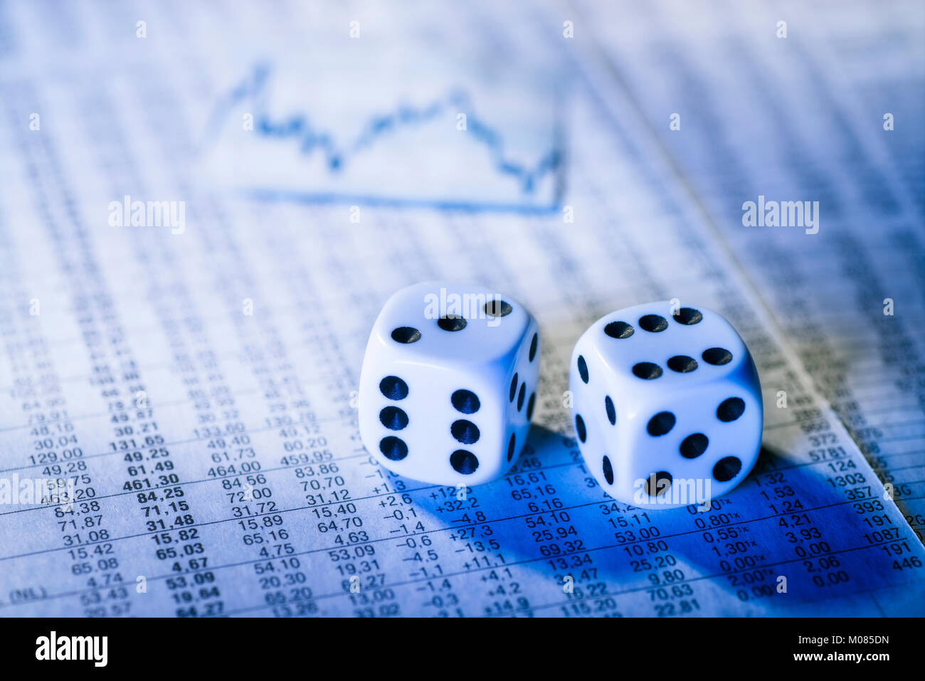 Two dice on a chart with stock prices - Stock Image