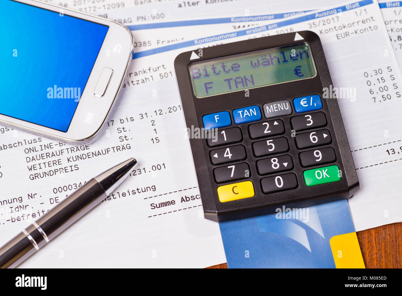 Tan generator with check card and statement of bank account - Stock Image
