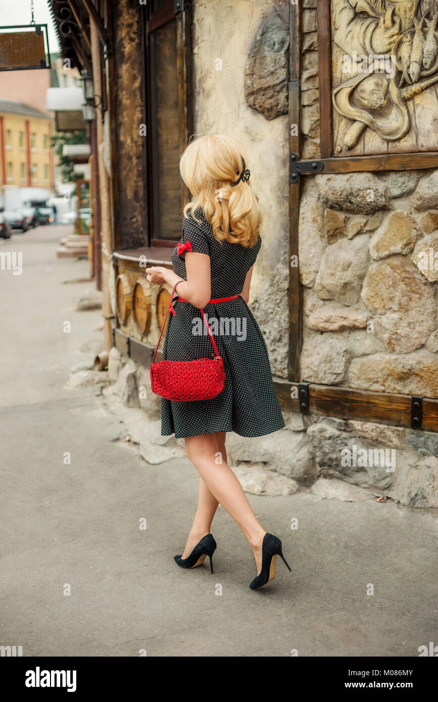 Blonde woman in a dress and heels walking down the street - Stock Image