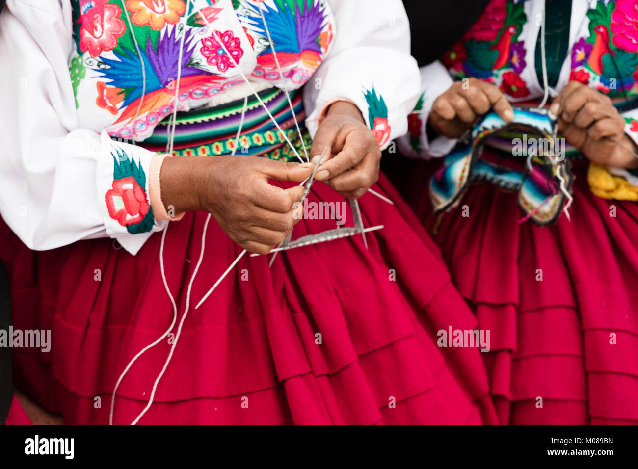 hands that sew typical costumes in Amantani on the Titicaca lake Stock Photo