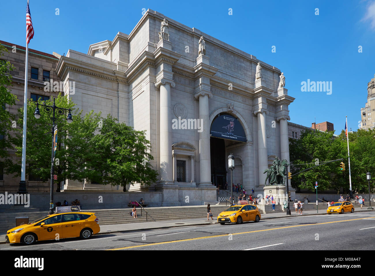American Museum of Natural History building facade with people and yellow taxi in a sunny day, blue sky in New York - Stock Image
