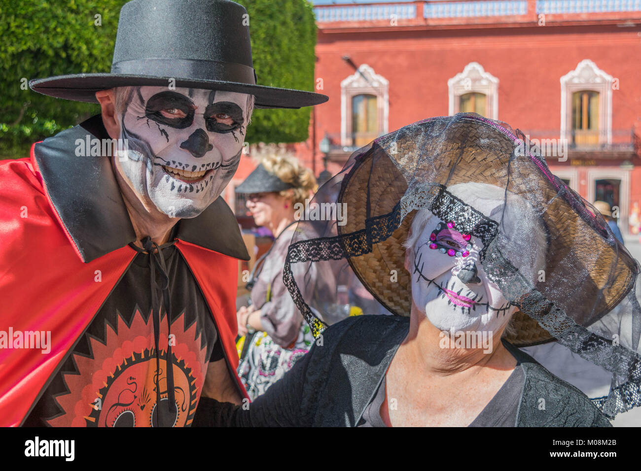 Man and woman in costumes with painted faces, a black bolero hat for him, and a straw hat with black veil for her, - Stock Image