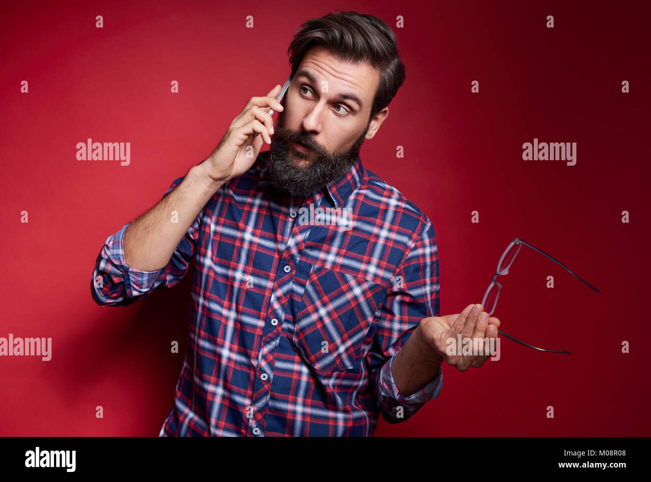 Puzzled man talking by mobile phone at studio shot - Stock Image