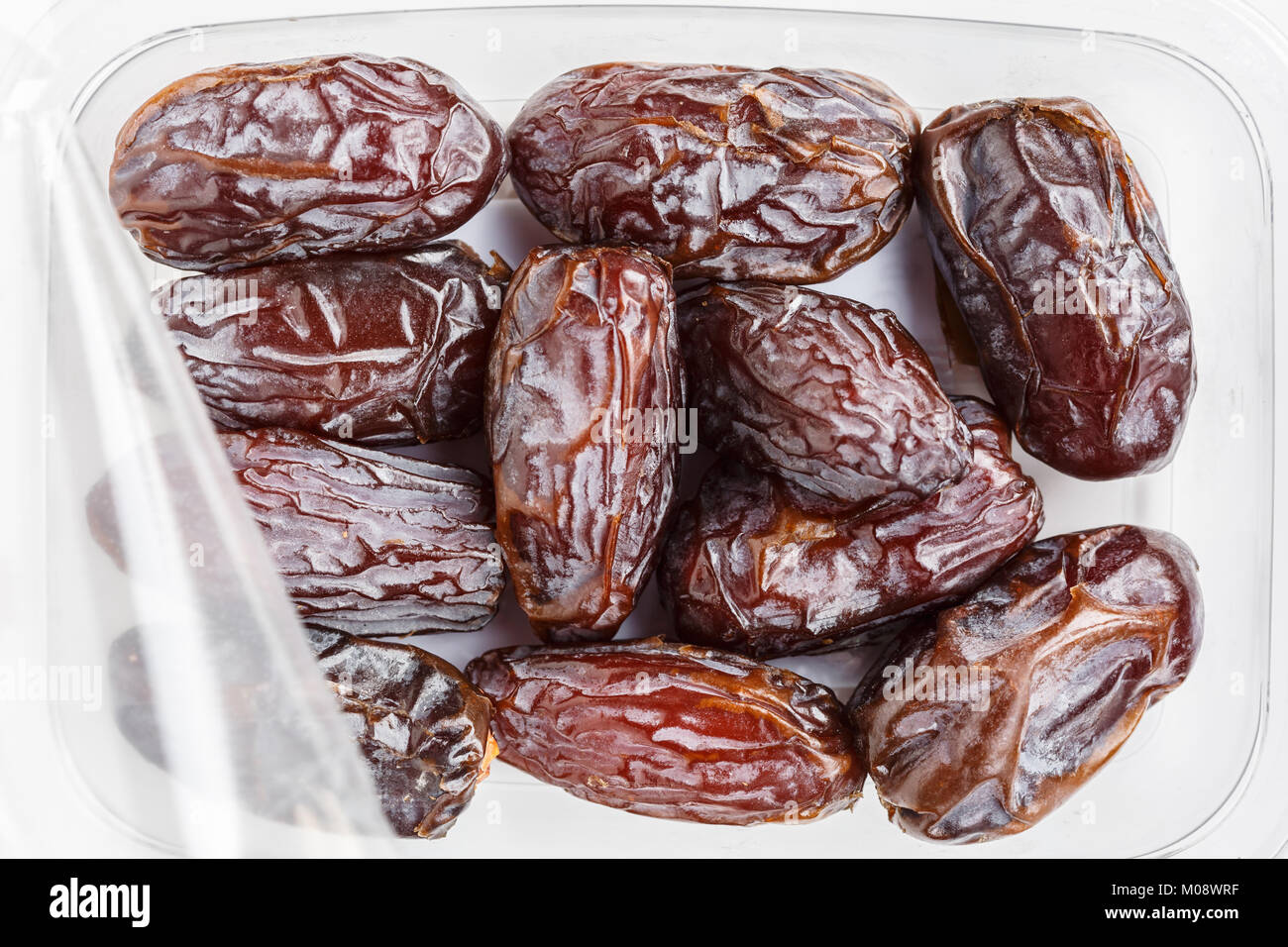 Medjool dates in a plastic container on white background - Stock Image