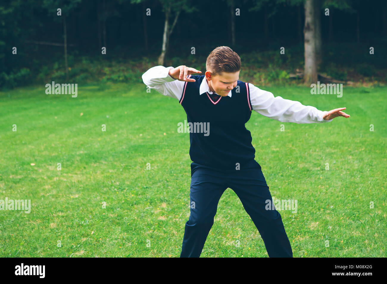A boy, teenager, schoolboy dressed up in formalwear imitates a fight in front of a forest on a lawn in summer. - Stock Image