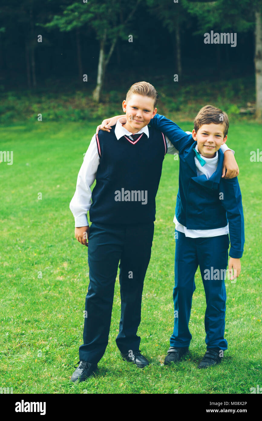 Two boys, brothers, schoolboys dressed up in formalwear with arms around each other in front of a forest on a lawn - Stock Image