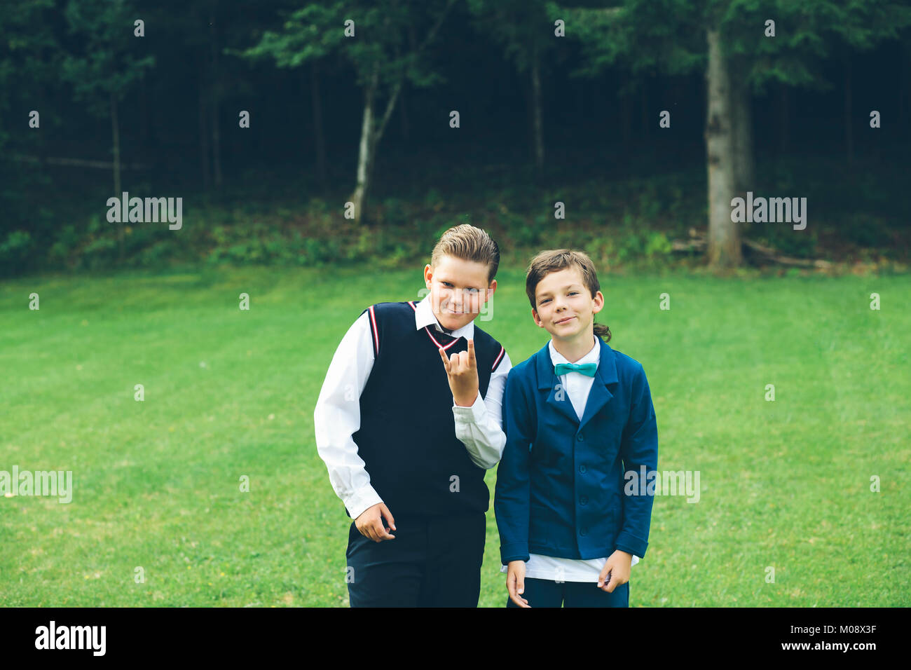 Two boys, brothers, friends dressed up in formal wear make fun in front of a forest on a lawn in summer. - Stock Image